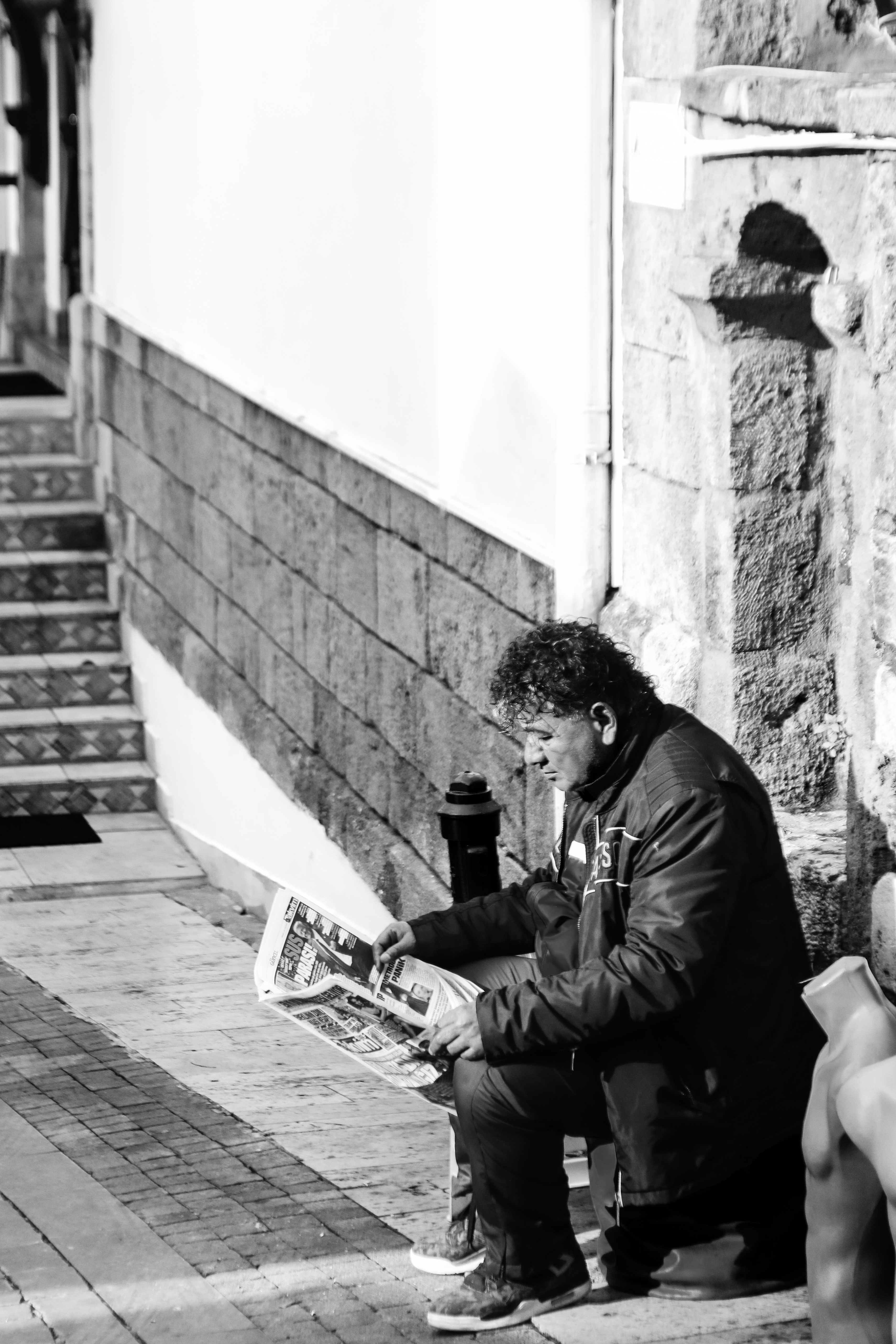 冬季午後在街角閲讀的中年男子